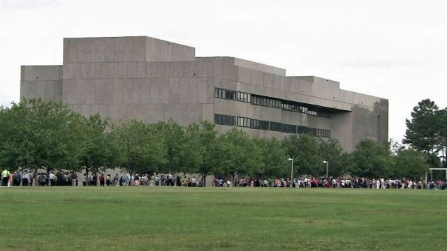 Workers line up outside the North Carolina Department of Revenue building in downtown Raleigh on Wednesday, Aug. 25, 2010. The building was evacuated after a suspicious-looking package was found.