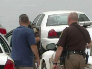 Durham County deputies put Derek O'Mary, left, into a patrol car on Sept. 8, 2010, after O'Mary, a former lieutenant in the Durham County Sheriff's Office, surrendered on embezzlement charges.