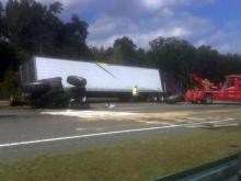A tow truck tries to remove a tractor trailer from northbound I-95 in Cumberland County on Oct. 26, 2010. The truck hit a mower cutting grass on the highway median, killing the mower operator.