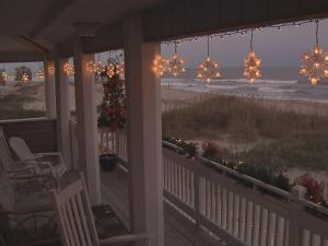 Lighted snow flakes hang on the porch that faces the ocean.