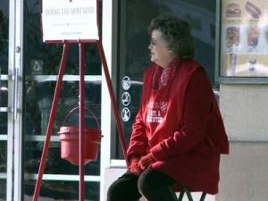 A Salvation Army volunteer sits by a collection kettle outside the Carolina Premium Outlets in Smithfield on Dec. 17, 2010.