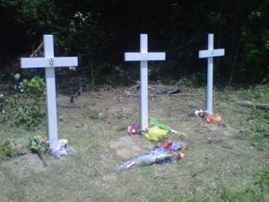 Crosses mark the site where three Wake Forest-Rolesville High School students were killed Sunday evening in a car crash while returning home from church.