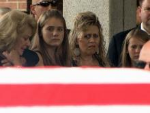 The family of Nash County Deputy Warren Lewis looks on at his flag-draped coffin on June 13, 2011.