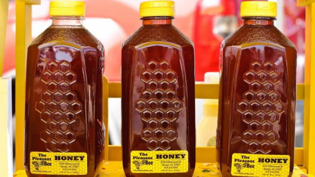 The Pleasant Bee displays jugs of honey during the Midtown Farmers Market at North Hills in Raleigh on September 3, 2011.