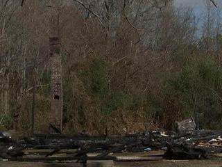 Only charred wood remains of the house where three men died Nov. 26, 2011.