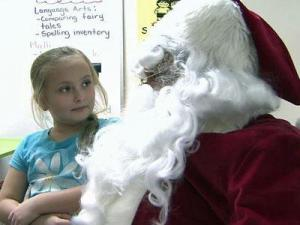 Bethany Arnold, a second-grader at Tar River Elementary School in Franklinton, is surprised by her father who is dressed as Santa.