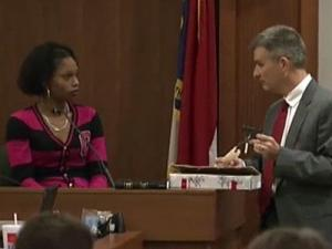 Orange County District Attorney shows pieces of a .25-caliber pistol to Shanita Love during testimony Dec. 9, 2011, in the trial of Laurence Lovette. Love testified that Lovette disposed of the pieces in her presence in three different spots in Durham three days after Eve Carson was shot and killed in Chapel Hill.