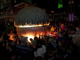 A crowd rushes forward to touch the acorn during First Night.