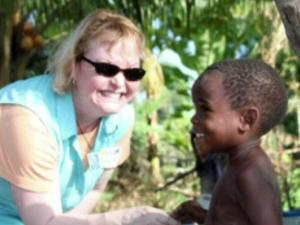 LuAnn Charlton poses with a child at the Hearts and Hands Children's Home in Haiti.