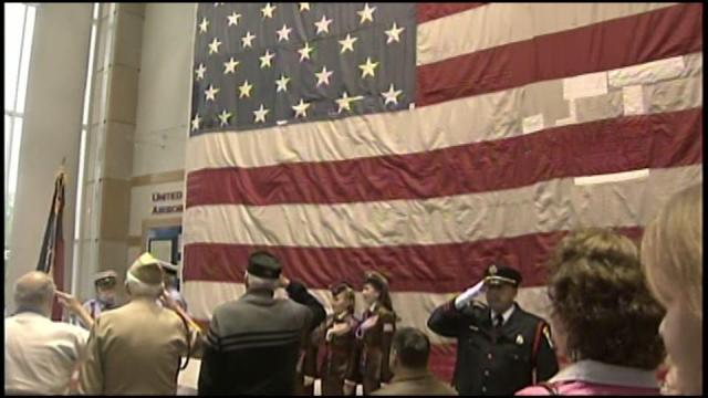 An American flag, damaged on Sept. 11, 2001, was unfurled in Fayetteville Friday.