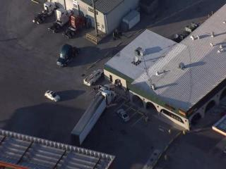 A tractor trailer rolls into a car and a building in Dunn after the driver forgot to set the parking brake.
