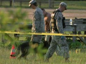 Army investigators look for evidence in a field where a soldier from the 525th Battlefield Surveillance Brigade shot and killed another member of the unit and then turned the gun on himself during a unit safety briefing on Thursday, June 28, 2012.