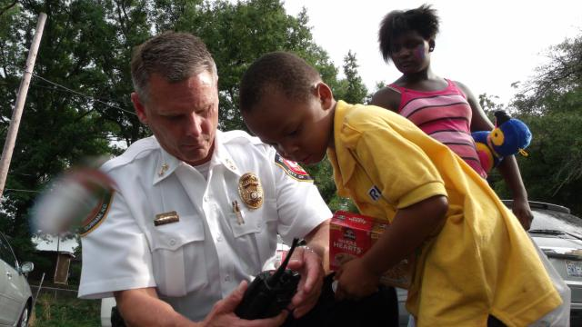 Deputy Chief Larry Smith shows a young boy his police radio at a National Night Out event in Durham.