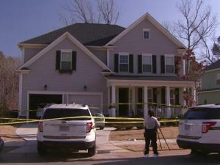 Police investigate the shooting deaths of a married couple at a Holly Springs home on Monday.