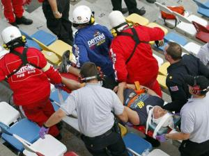 Paramedics at Daytona International Speedway take Dan Germeroth, of Angier, N.C., for treatment after he was hit by flying debris from a crash in the last lap of the NASCAR Nationwide Series race.