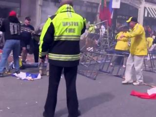 Authorities try to get to injured spectators near the finish line of the Boston Marathon after two homemade bombs exploded on April 15, 2013.