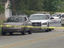 Crime scene tape surrounds two Fayetteville police cruisers and a car after a May 1, 2013, shooting on Sourwood Drive involving a police officer.