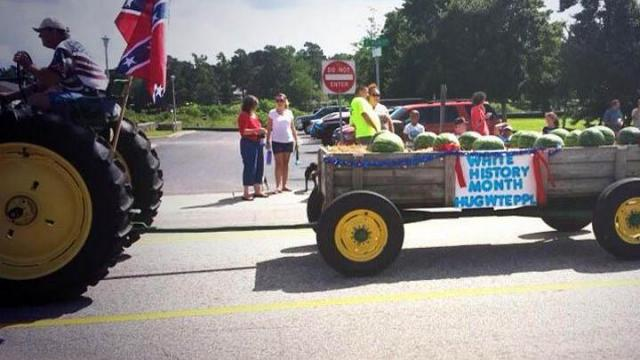"Farmer Donnie Spell, who has driven his tractor in the Hope Mills Independence Day parade for years, tacked a sign saying ""White History Month - Hug Wht Ppl"" to a trailer filled with watermelons that he pulled down Main Street during the July 4, 2013, event. (Photo from Twitter)"