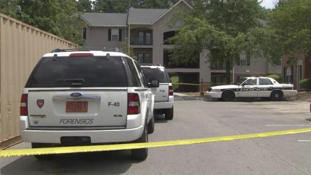 Crime scene tape surrounds an apartment building at Greens of Pine Glen in Durham on July 24, 2014, a day after police found Ella Davis, 58, dead inside her home.