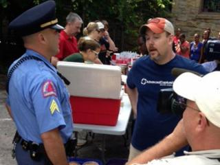A Raleigh police officer speaks with a volunteer with Human Beans Together on Sunday, Aug. 25, 2013, about feeding the homeless.