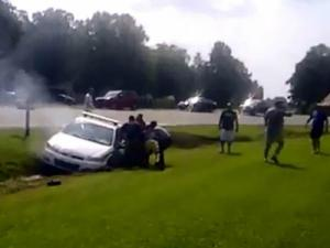 An image from a cellphone video shows people trying to pull Officer Ashley McLamb from his Wilson's Mills patrol car after he crashed into a drainage ditch on Sept. 1, 2013. (Photo courtesy of Kathy Hoffman)