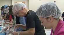 Volunteers help to package meals for Stop Hunger Now