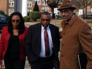 Former UNC-Chapel Hill professor Julius Nyang'oro, center, surrenders to Orange County authorities on Dec. 3, 2013, after his indictment on a charge of obtaining property by false pretense. Nyang'oro is accused of taking money for a class that he never taught. He is accompanied by his wife and attorney Butch Williams.