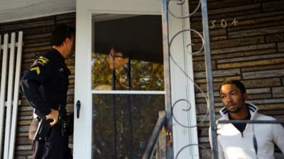 Officers Ronny Hassell and Rachel Juren talk while searching a home in High Point where drug activity had been reported.