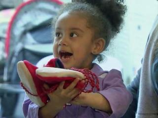 A child at the Durham Rescue Mission unwraps a gift. The charity is about 1,000 toys short of what it needs for its annual Christmas giveaway to help those in need in the community.
