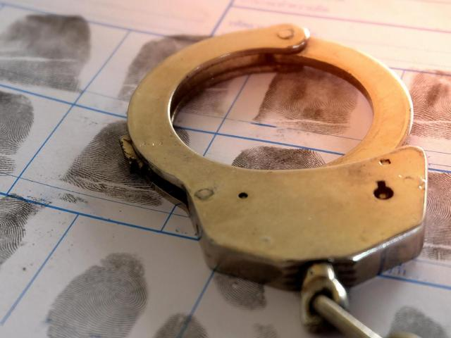 Handcuffs resting on top of a page of fingerprints <br/>Web Editor: Alfred Charles