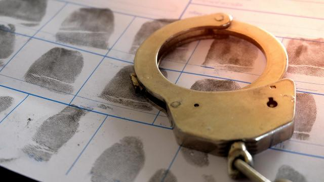 Handcuffs resting on top of a page of fingerprints
