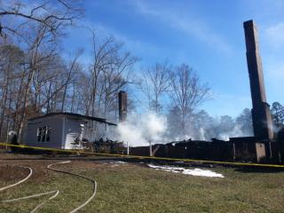 Fire smolders at 5445 Denberg Lane near Cary on Monday morning, Jan. 13, 2014, more than 12 hours after a fire destroyed the home. (Bill Herrero/WRAL)