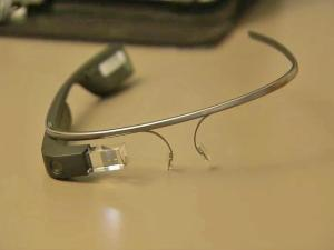 Google Glass is a wearable, voice-controlled computer with an optical head-mounted display and built in video camera. Glass delivers an augmented reality image to the wearer. It can search the internet, answer dictated questions, take pictures and record video.