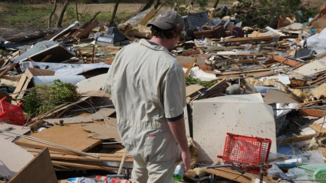 Corey Bryan surveys storm damage to a mobile home on his family's Wayne County farm on Saturday, Feb. 22, 2014.