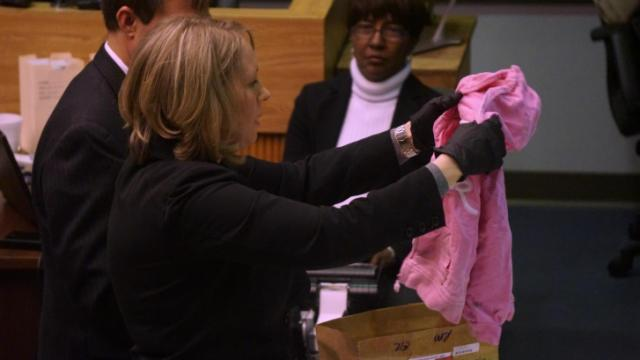 Charlotte Fournier, a former crime scene investigator for the Johnston County Sheriff's Office, holds up a child's jacket for jurors in the capital murder trial of Jonathan Richardson on March 4, 2014. (Chad Flowers/WRAL)