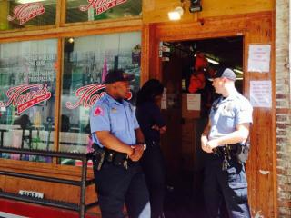 Officers  stand outside while investigators search Hannah Stop  'n' Go on Wilmington Street on April 22, 2014.