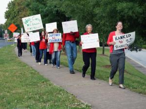About 60 teachers from Apex High School rallied outside their school Wednesday morning to speak out about compensation and dwindling teacher morale.