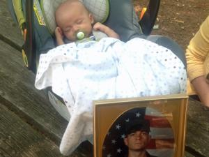 Patrick Walston sleeps near a photo of his father, Brian Walston. The Army veteran, died from colon cancer, experienced delays at the Durham VA Medical Center, according to his wife.