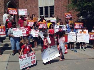 People rally outside a job fair aimed at Wake County teachers that was put on Saturday, May 31, 2014, by the Houston, Texas school district.
