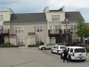 Crime scene tap and police cars surround a Durham residential building on July 3, 2014, after a fatal shooting.