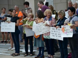 Dozens rallied in Chapel Hill on Monday in support of allowing tens of thousands of children entering the United States illegally to remain in the country. (Adam Owens/WRAL)