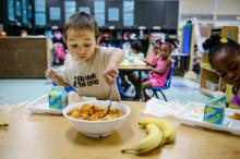Sterling Richard, 3, serves himself potatoes for breakfast at McClure Early Childhood Education Center in Tulsa. The city has 13 such programs providing  preschool on property next to public schools. (Photo by James Robinson/The Fayetteville Observer)