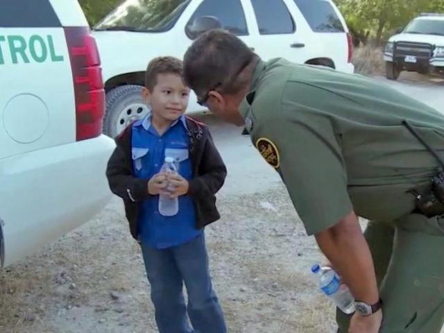 A child talks with a Border Patrol officer after crossing the Mexico/U.S. border alone.<br/>Photographer: Zac Gooch