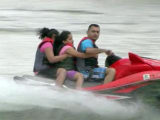 A man carries a woman and child on a watercraft on the Rio Grande.