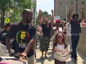 Dozens rallied and marched in downtown Raleigh Sunday for Michael Brown Jr., the Missouri teen shot and killed by Ferguson police on Aug. 9.
