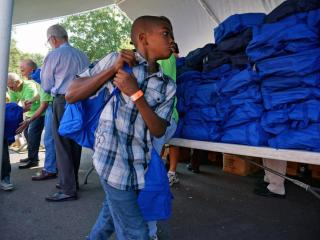 Volunteers at the Durham Rescue Mission gave away more than 3,600 backpacks with school supplies and 12,000 pieces of clothing on Friday, Aug. 21, 2014, at the 15th annual back-to-school party.