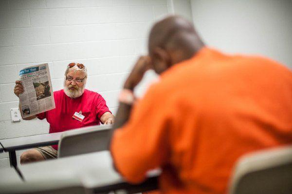 A tutor with the Cabarrus Literacy Council helps inmates at the Cabarrus County Detention Center with reading skills during a class.  Credit: James Nix, The Independent Tribune Literacy Council