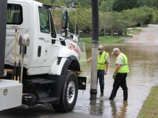 Workers pump water off Durham Drive in Raleigh on Sept. 9, 2014.
