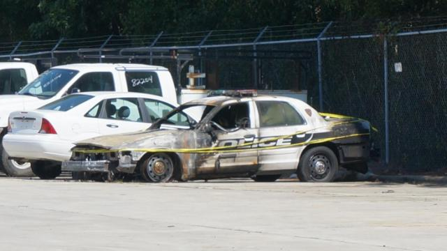 A Durham police car (in the foreground) was set on fire early Sunday, Sept. 21, 2014, at 3000 Old Trail Drive.