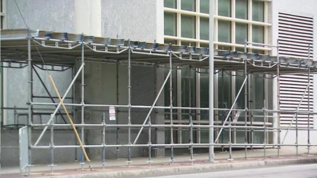 Safety barriers and warning signs went up Monday outside two buildings in downtown Raleigh due to falling glass.